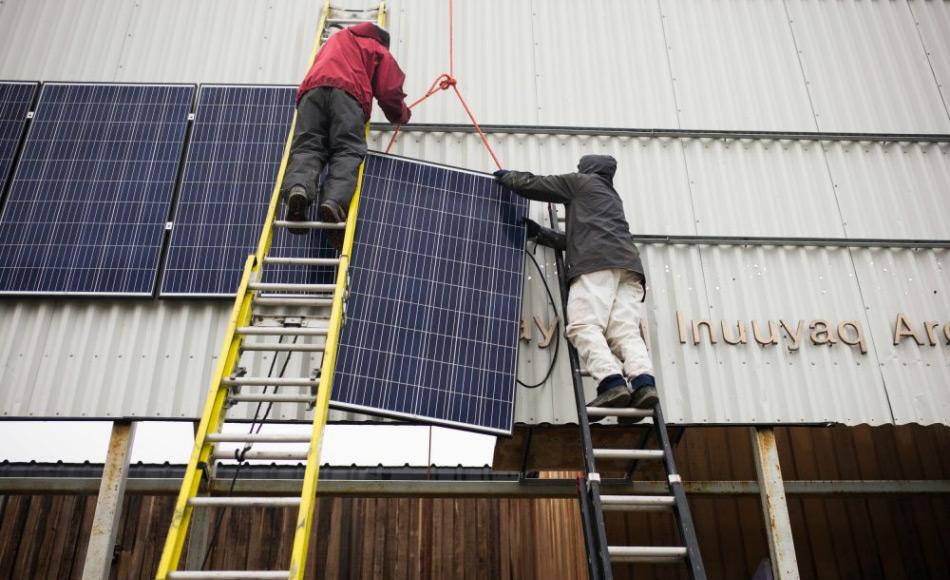 Der Ingenieur Duncan Martin (links) von Vancouver Renewable Energy Coop und der Logistik-Koordinator von Greenpeace Canada, Claude Beausjour, installieren Solarpanels an der Fassade des Gemeindezentrums von Clyde River. Bild: Greenpeace